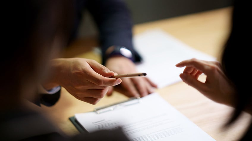 Close-up of a person passing a pen to another person who has documents on the table in front of them. Edges of photo are blurry, with emphasis only on swapping pen between hands